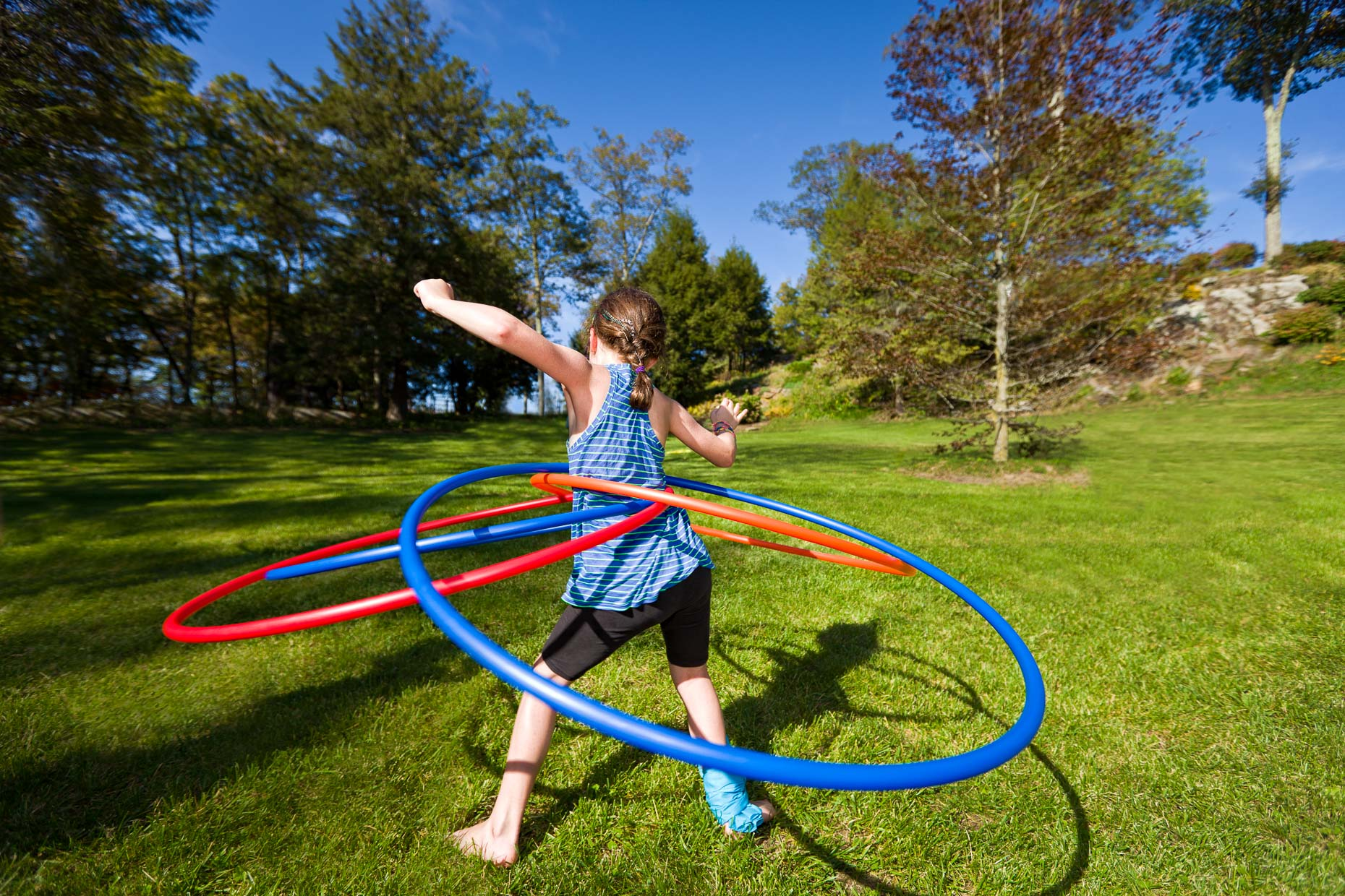 Young girl in park spinning four hula hoops on a sunny day