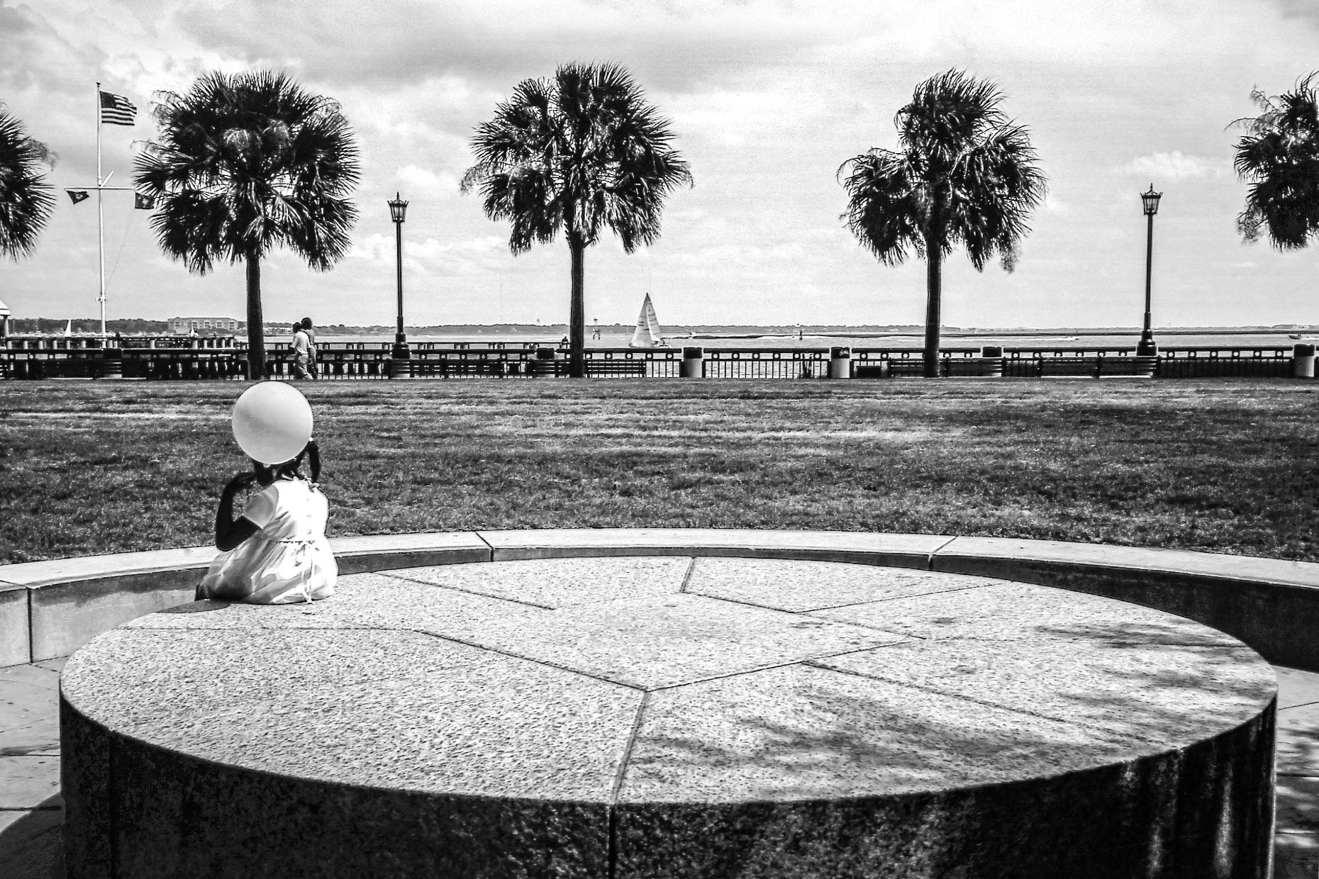 Black and white photograph of young girl with balloon sitting on round concrete bench with palm trees and ocean in background