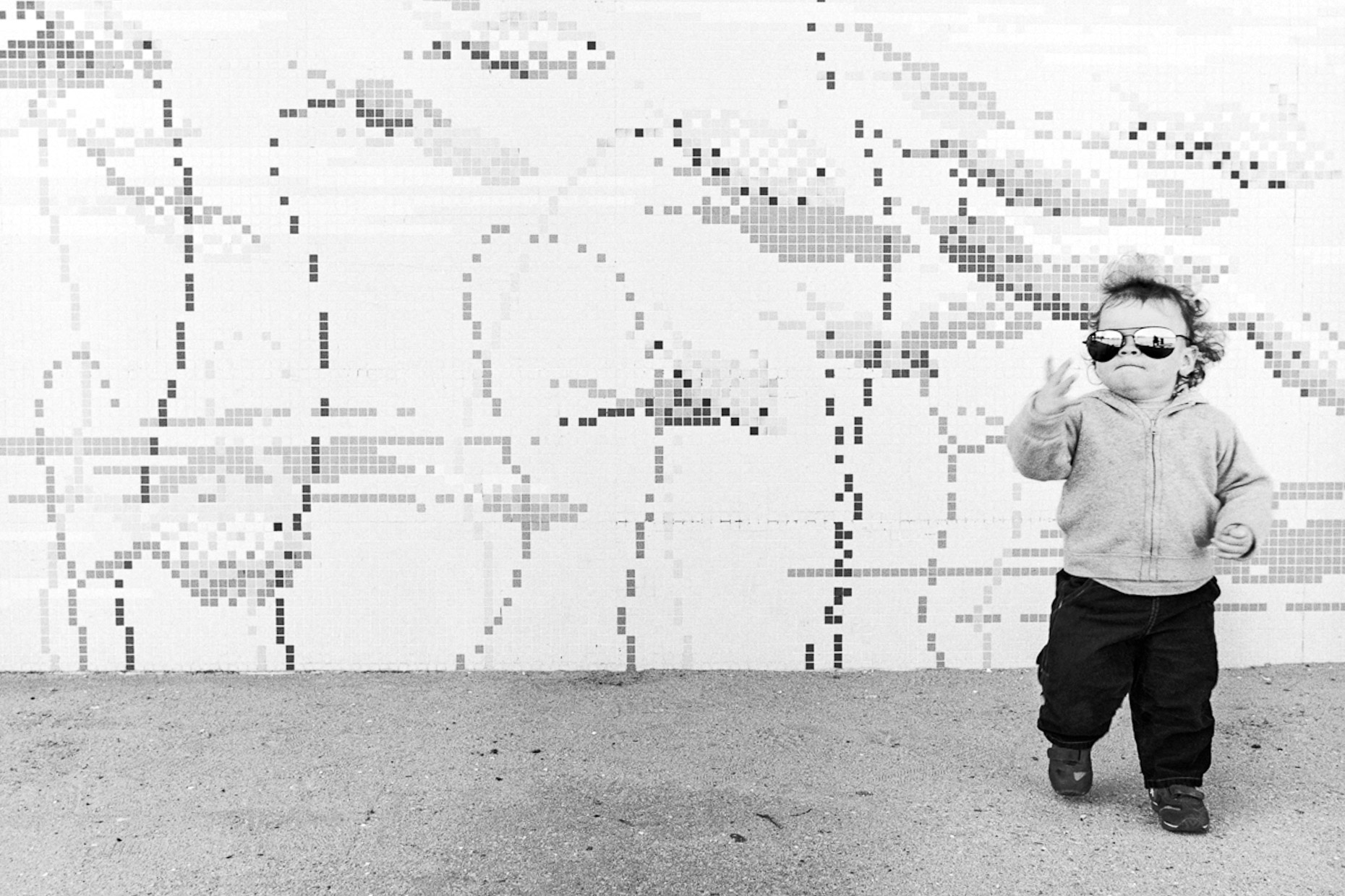 Black and white photograph of little boy wearing sunglasses in front of mosaic wall
