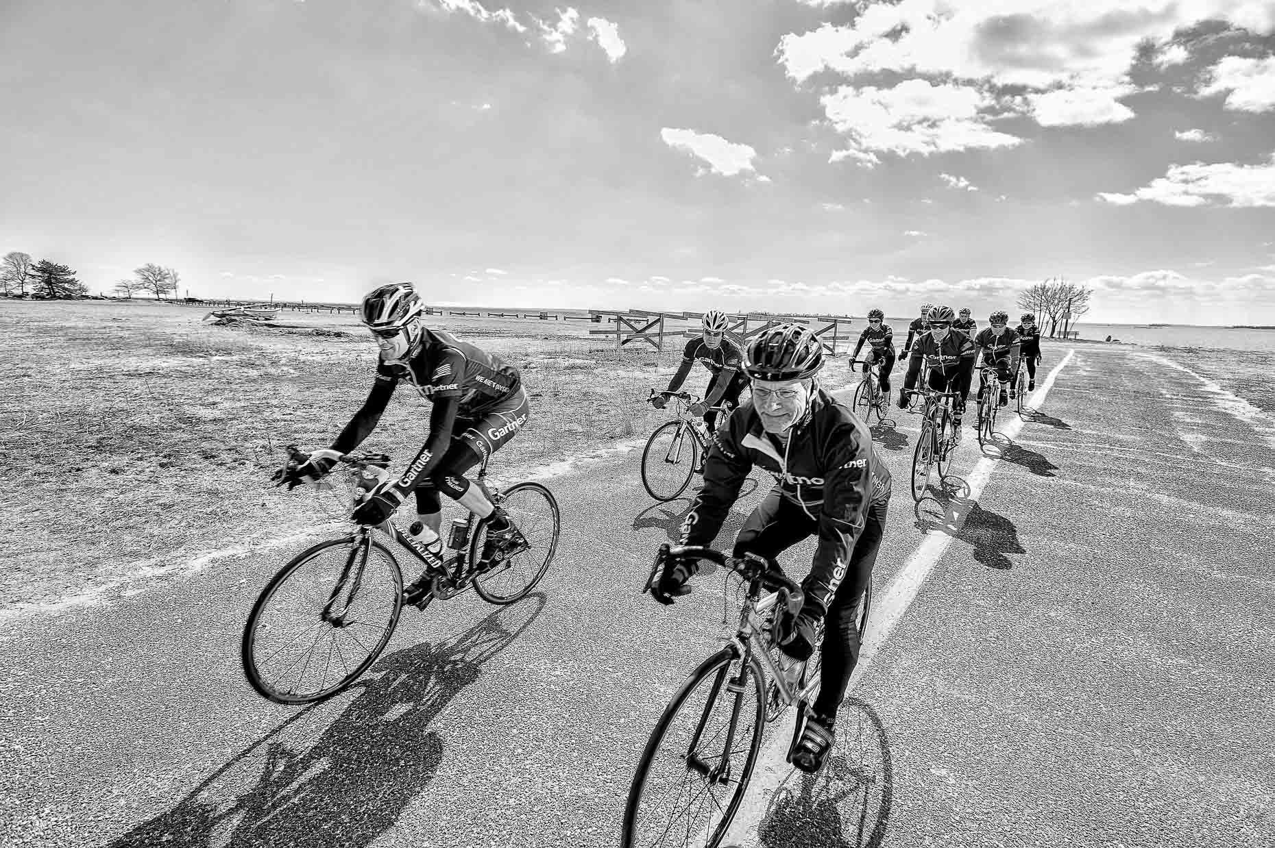 Black and white photograph of cycling team wearing Gartner jerseys and riding bicycles on Connecticut shore