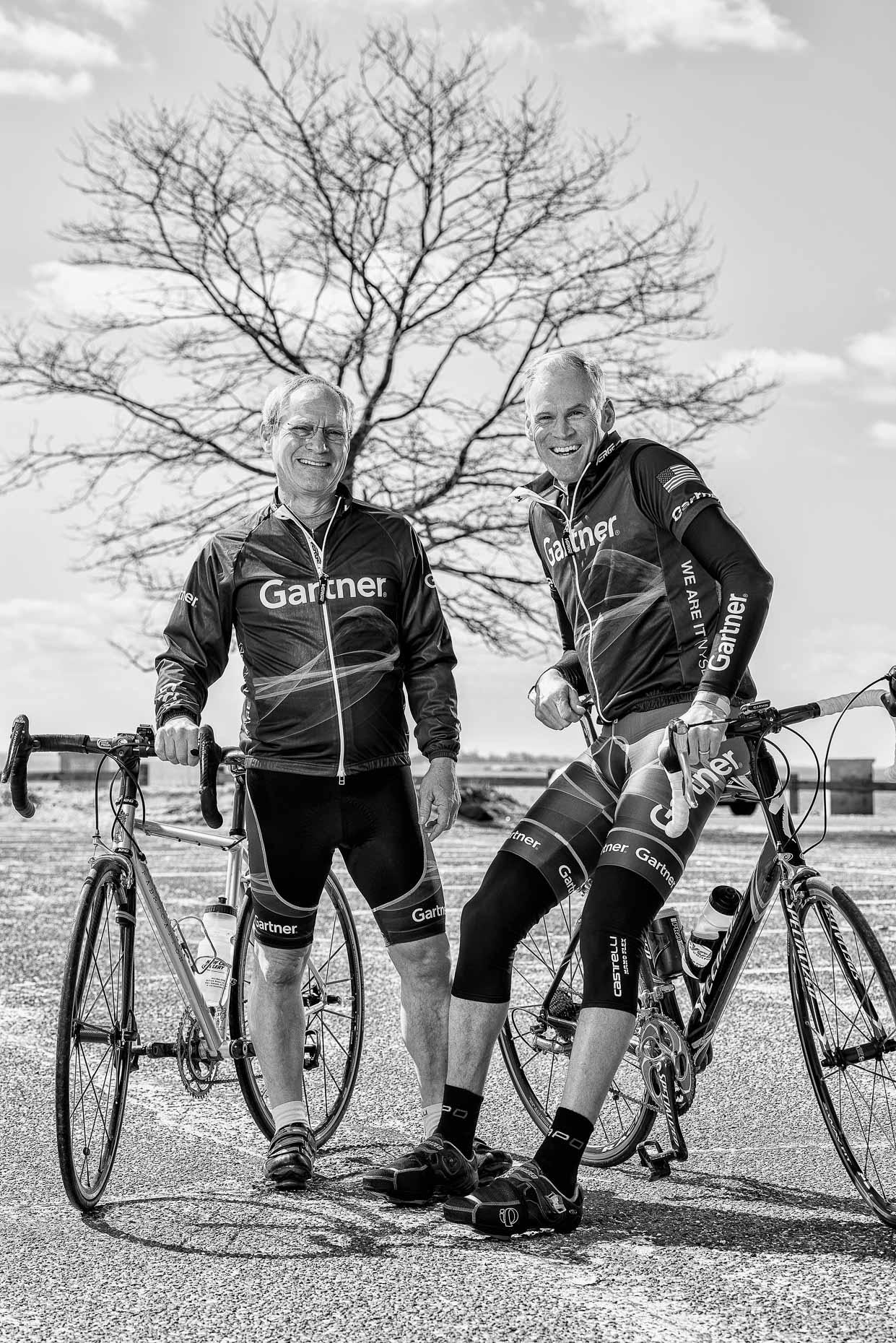 Two men with bicycles wearing Gartner bike jerseys and shorts in front of large tree