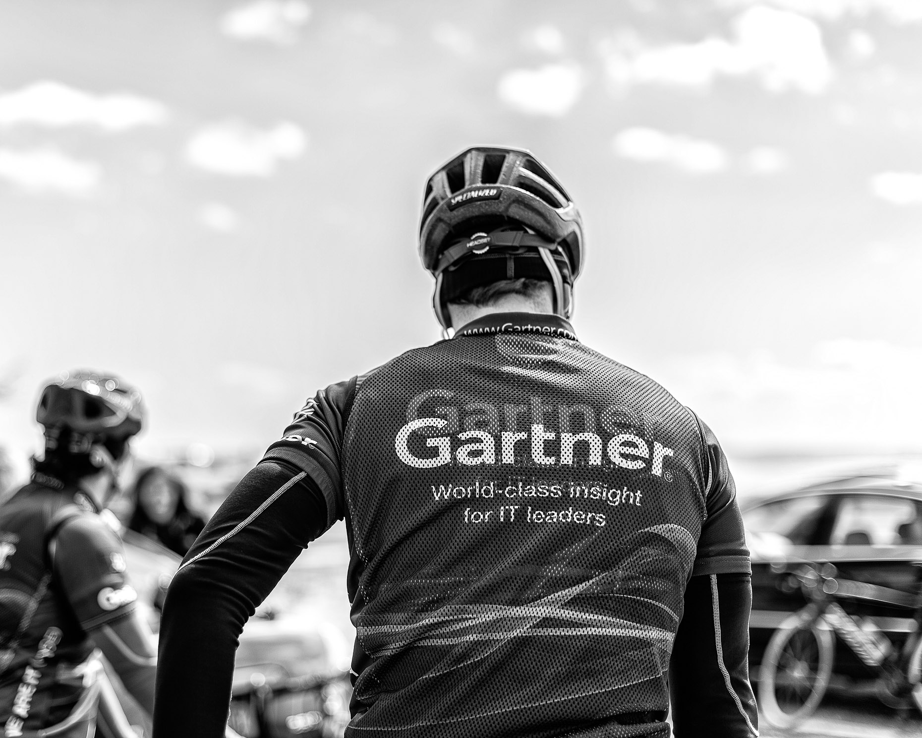 Black and white photograph of man on bicycle wearing mesh gartner jersey and helmet