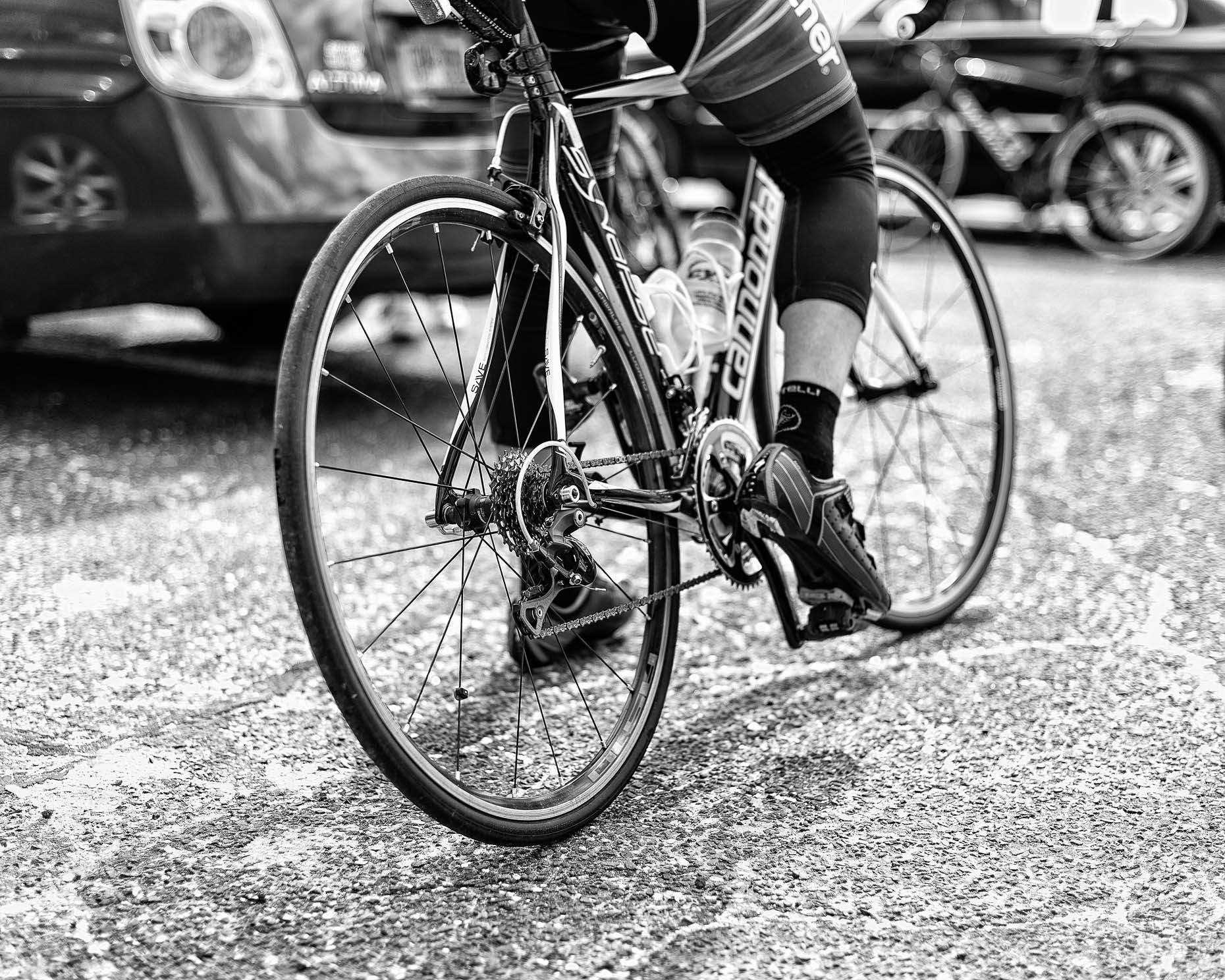 Black and white photograph of man in Gartner bike shorts sits and leans on bicycle in parking lot