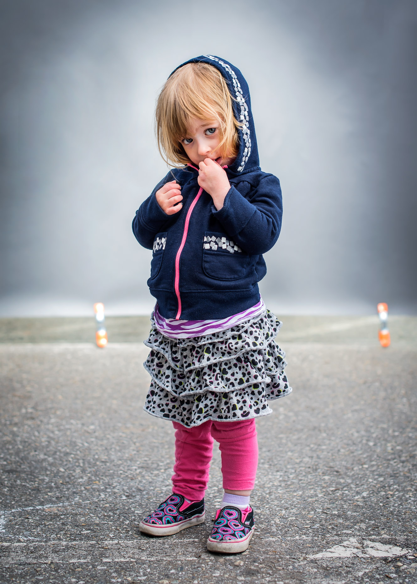 Shy little girl in blue hoodie and ruffled skirt in front of grey background