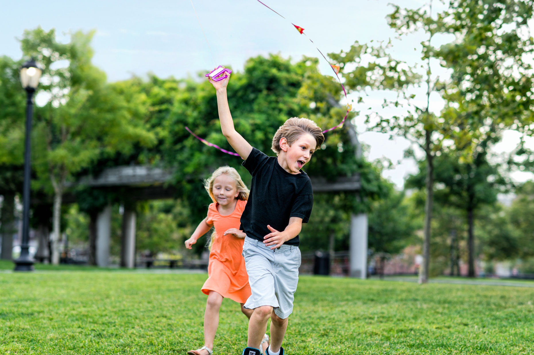 Brother and sister running in park while flying kite in Boston Massachusetts