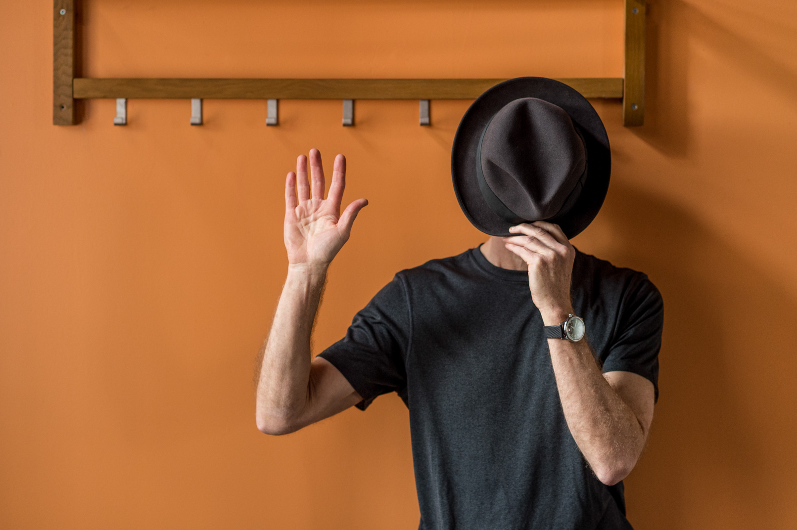 Man stands with hat in front of face in front of orange wall